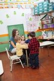 Teacher Playing With Children In Kindergarten. Young preschool teacher playing with children in kindergarten Stock Photos