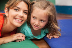 Teacher playing on the floor with a litlle girl Stock Photos