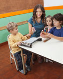 Teacher Playing Musical Instruments With Children. Young teacher playing musical instruments with children in classroom Royalty Free Stock Photo