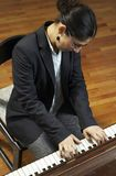 Teacher Playing Piano Keyboard. Portrait of a female piano teacher looking downward as she plays piano.  Taken from high viewpoint Stock Photos