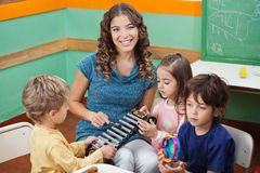 Teacher Playing Xylophone With Students In. Portrait of young teacher playing xylophone with students in preschool Royalty Free Stock Images