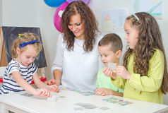 Teacher plays with children Stock Photography