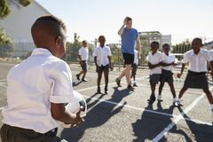 Teacher plays football with young kids in school playground Stock Image