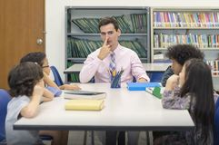 Teacher point at his nose and teaching body parts on facial. Group of Preschool child happy and intend learnig at classroom.  stock photos