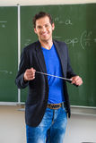 Teacher with pointer in front of a school class Stock Photos
