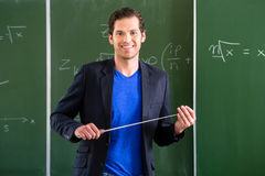 Teacher with pointer in front of a school class Royalty Free Stock Photos