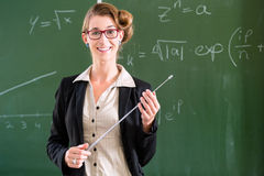Teacher with pointer in front of a school class Stock Images
