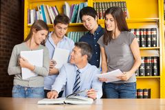 Teacher Pointing At Book While Discussing With Royalty Free Stock Image