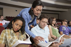 Teacher Pointing In Book While Student Looking. Teacher pointing in book with pen while student looking and classmates Stock Photos