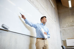 Teacher pointing marker to white board at lecture. Education, school, business, teaching and people concept - happy teacher or businessman pointing marker to Stock Images