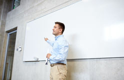 Teacher pointing marker to white board at lecture Stock Images