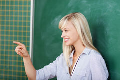 Teacher pointing on someone in the classroom stock photography