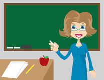 Teacher pointing to chalkboard Royalty Free Stock Photos