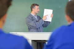 Teacher pointing to paperwork Royalty Free Stock Photos