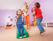 Teacher points running and jumping kids to viewer Royalty Free Stock Photo