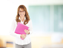 Teacher portrait. Portrait of middle age teacher holding files and standing at classroom at school Stock Images