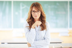 Teacher portrait. Middle age teacher standing in front of blackboard at classroom Royalty Free Stock Images