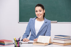 Teacher. Portrait of a young smiling teacher in classroom stock image