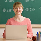 Teacher posing with laptop in school classroom Royalty Free Stock Photography
