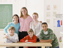 Teacher posing with students. Teacher and her students pose together in the classroom Stock Images