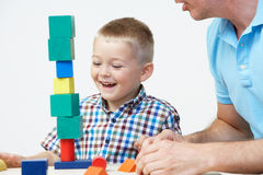 Teacher And Pre-School Pupil Playing With Wooden Blocks Stock Photo