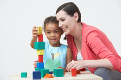 Teacher And Pre-School Pupil Playing With Wooden Blocks Royalty Free Stock Photography