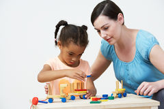 Teacher And Pre-School Pupil Playing With Wooden House Royalty Free Stock Images