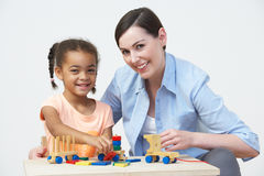 Teacher And Pre-School Pupil Playing With Wooden House Stock Images