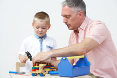 Teacher And Pre School Pupil Playing With Wooden Tools Stock Images