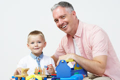 Teacher And Pre School Pupil Playing With Wooden Tools Stock Photo