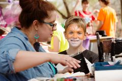 Teacher works beside young actor. Teacher prepares makeup for a young actor who smiles at the camera Stock Image