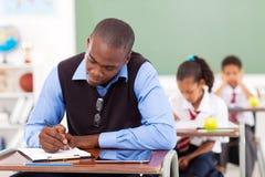 Teacher preparing lesson. African American primary school teacher preparing a lesson in classroom Stock Photo