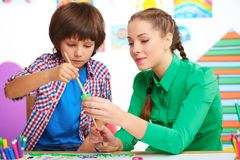 Teacher in preschool center helping boy to draw Stock Photos