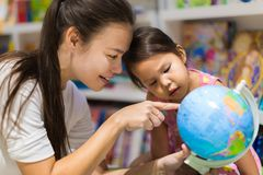 A teacher and a preschool student learning geography on a world globe. Mother showing her daughter something on the globe inside of a bookstore royalty free stock images