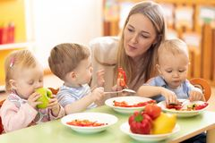 Teacher and preschooler kids having break for fruits stock photography