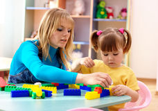 Teacher and preschooler play with building bricks. In playroom stock photo