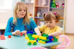 Teacher and preschooler play with building bricks Royalty Free Stock Photos