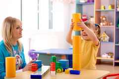 Teacher and preschooler play with building bricks. In playroom royalty free stock photos