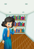 A teacher presenting the books in the bookshelves Royalty Free Stock Images