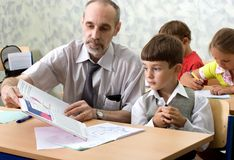 Teacher and pupil. The teacher and the pupil sit at a school desk study the alphabet Stock Photos
