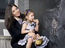 Teacher with pupil in classroom at blackboard writting, mother and daughter first time to school Stock Images