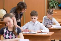 Teacher and pupil in classroom learning together. Kid looks together with teacher in book. This tells child the task. Royalty Free Stock Photography