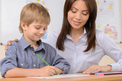 Teacher with pupil. Confident schoolboy writing something in note pad while sitting near his teacher Royalty Free Stock Image