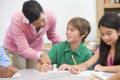 Teacher and pupil in elementary school classroom. Working on written project Stock Image