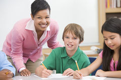 Teacher and pupil in elementary school classroom. Working on written project Royalty Free Stock Photos
