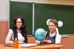 Teacher and pupil in geography class. Royalty Free Stock Photos