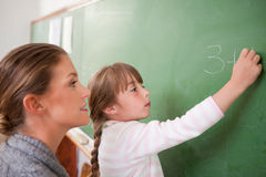 Teacher and a pupil making an addition Stock Images