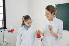 Teacher with pupil making experiment in class. Teacher with pupil making experiment in chemistry class stock photos