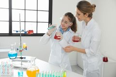 Teacher with pupil making experiment in class. Teacher with pupil making experiment in chemistry class stock photography
