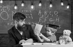 Teacher and pupil in mortarboard, chalkboard on background. Father teaches son elementary knowledge, discuss, explain. Elementary education concept. Kid royalty free stock photography